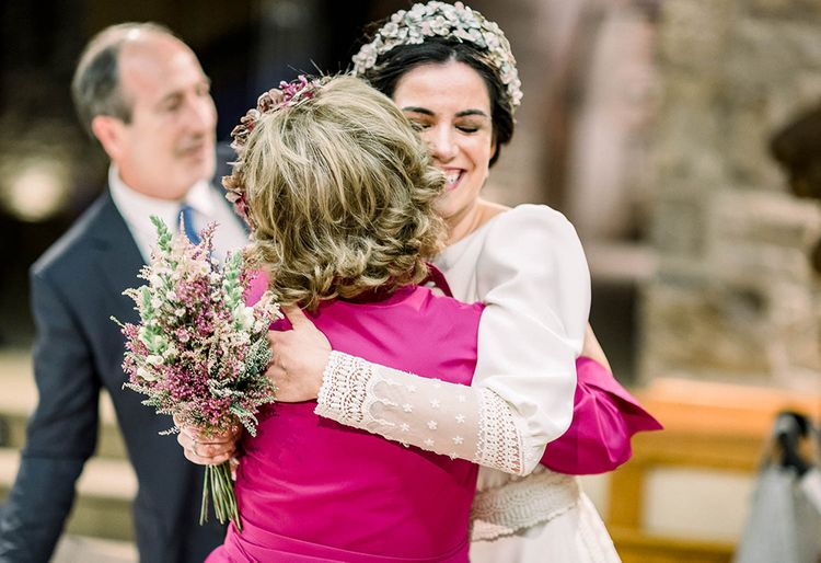 Bride hugging a wedding guest holding her astilbe wedding bouquet