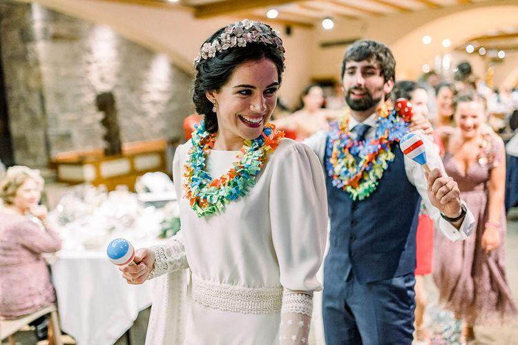 Bride and groom shaking maracas wearing colourful Hawaiian flower necklace