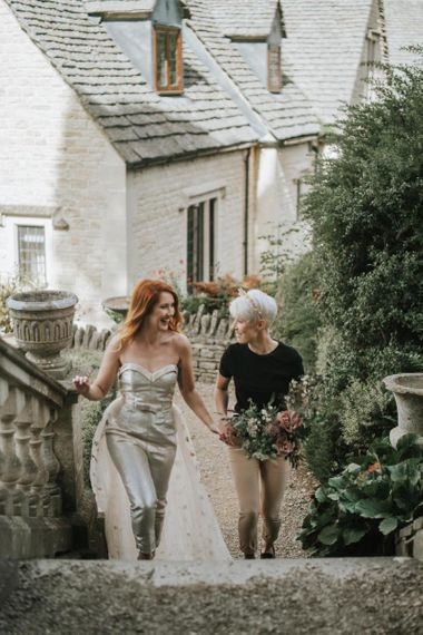 Bride in gold jumpsuit and bride in black t-shirt and beige trousers