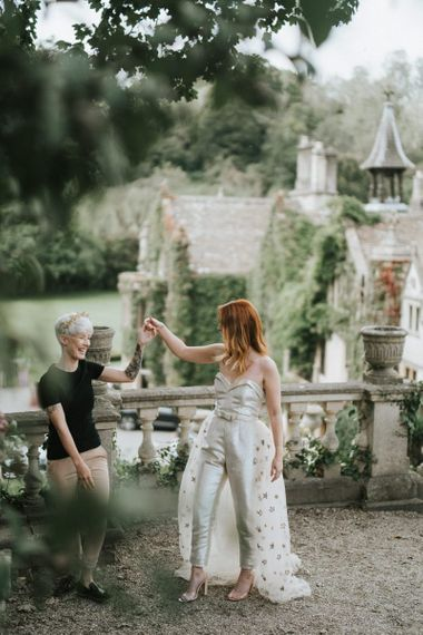Two brides dancing on the grounds of Castle Combe Manor House in Wiltshire