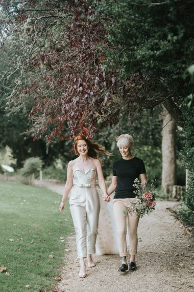 Same sex wedding couple walking through the grounds at Castle Combe Manor House in Wiltshire