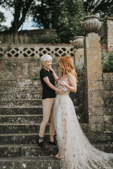LGBTQ+ wedding confetti moment with bride in bridal jumpsuit