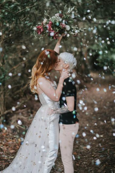 Brides kissing during confetti moment
