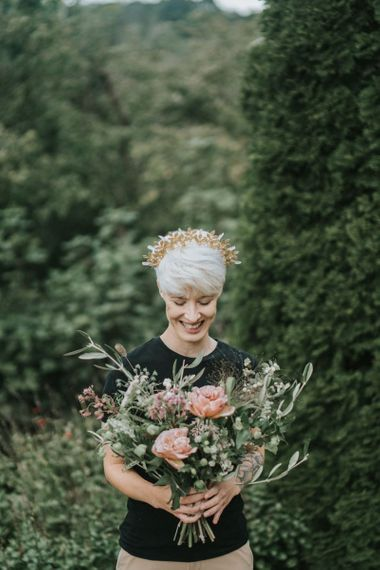 Bride with short hair wearing a gold crown and holding a bridal bouquet