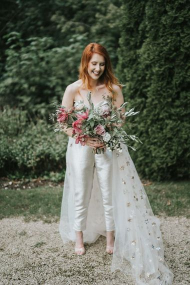 Bride in strapless bridal jumpsuit holding a romantic wedding bouquet