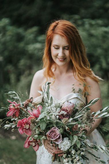 Bride with red hair holding a dusky pink wedding bouquet