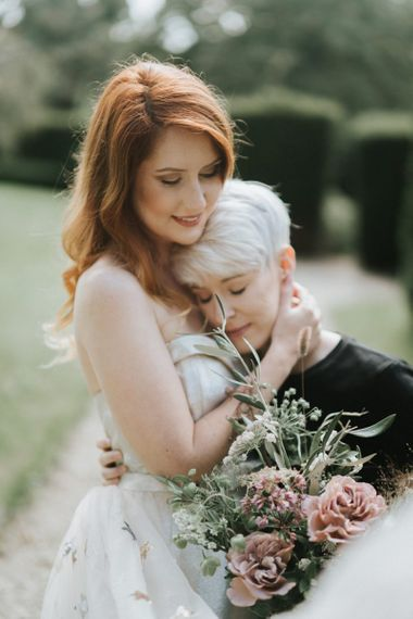 Bride and bride embracing at Castle Combe Manor House in Wiltshire