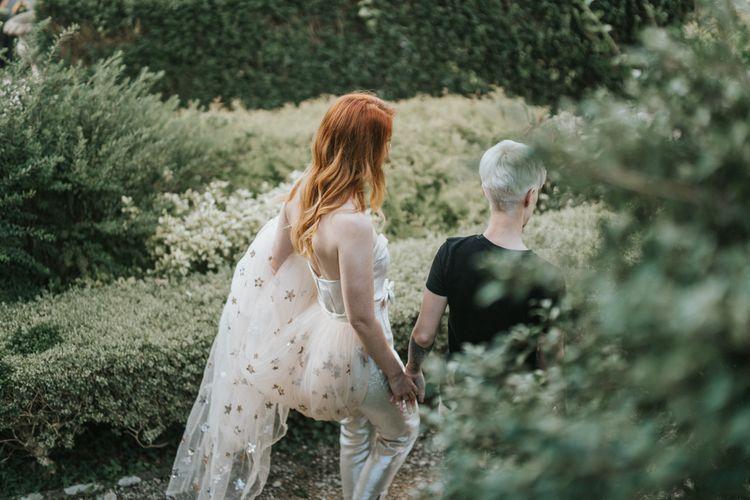 连身裤的新娘有金星盖的火车走通过花园的庭院在城堡Combe庄园议院在威尔特郡
