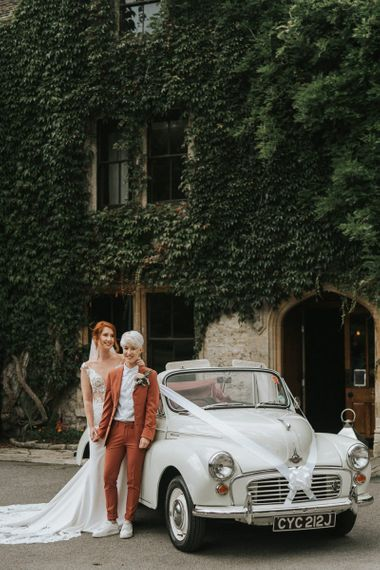 Two brides standing next to a morris Minor wedding cake