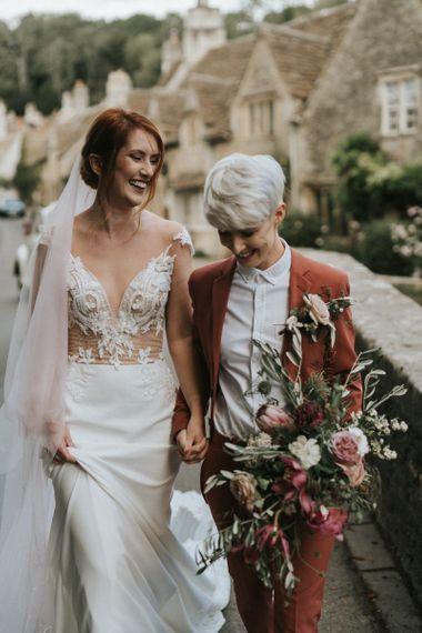 Brides holding hands walking through picturesque Wiltshire village