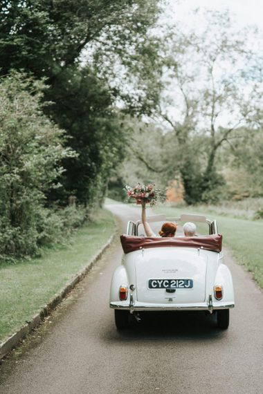 Brides riding off into the sunset in a convertible wedding car