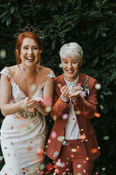 Two brides blowing confetti out of their hands