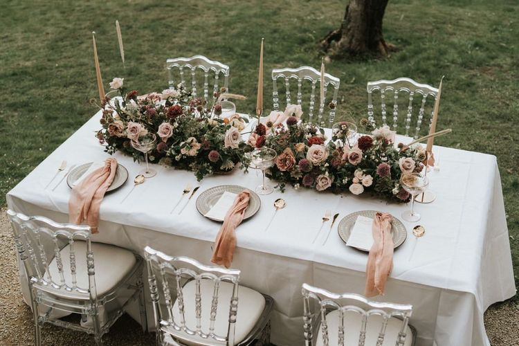 Intimate tablescape with floral centrepiece taper candles and ghost chairs