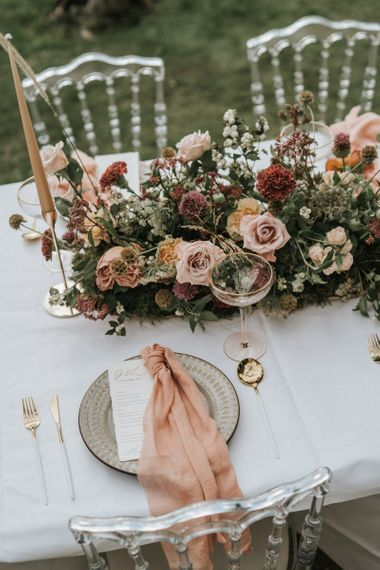 Wedding table decor with floral centrepiece, taper candles and gold cutlery