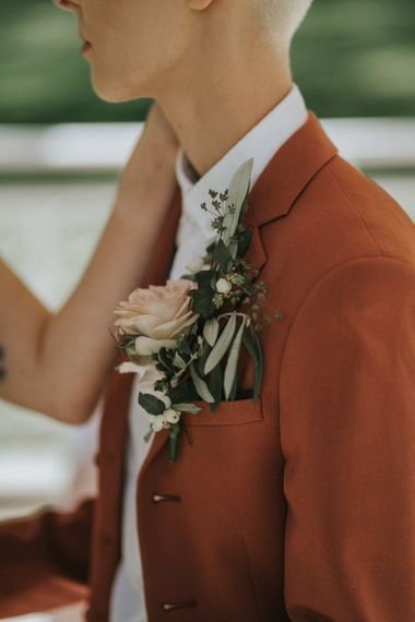Rust wedding suit and pink buttonhole