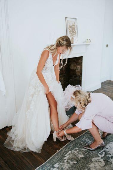 Bride in Enzoani wedding dress putting on her wedding shies