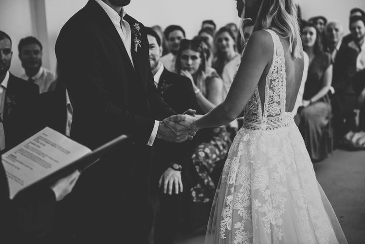 Groom holding his brides hands in a lace and tulle Enzoani wedding dress