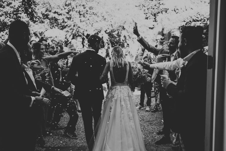 Black and white portrait of bride and groom exiting the Aswarby Rectory wedding ceremony