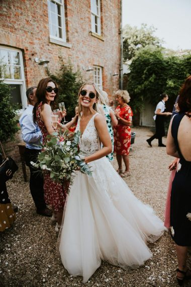 Stylish bride in lace and tulle Enzoani wedding dress and sunglasses
