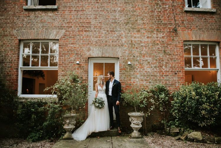 Bride in Enzoani wedding dress and groom in black suit at Aswarby Rectory wedding