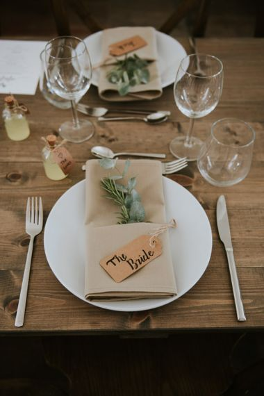 Place setting with napkin, foliage stem and luggage tag