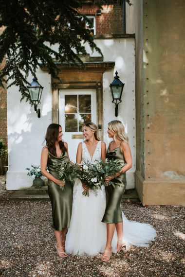Bridesmaids in sage green satin dresses and foliage bouquets