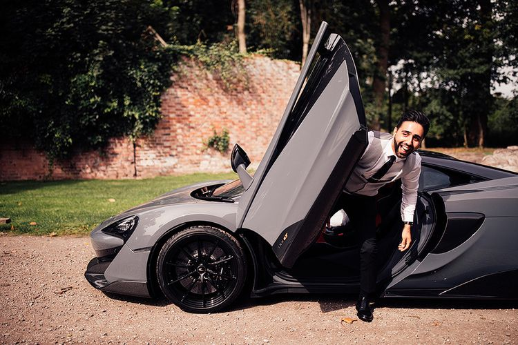 Groom stepping out of a sports car at Dorfold Hall wedding
