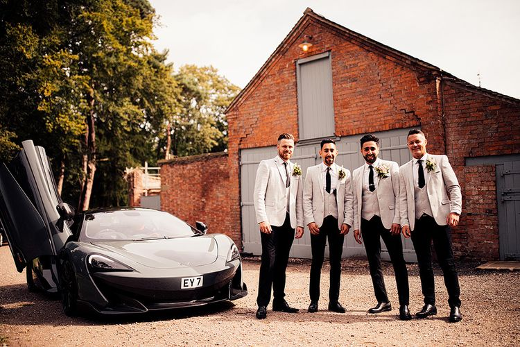 Groom and groomsmen in grey blazers and black trousers standing next to a sports car