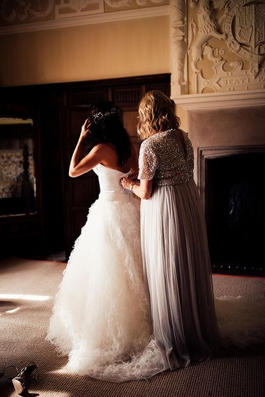 Bridesmaid helping the bride into her wedding dress