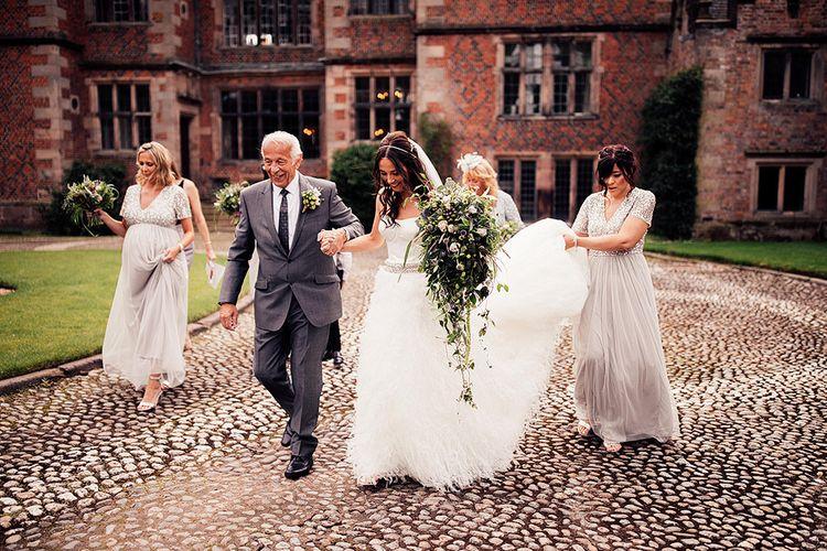 Bridal party walking through Dorfold Hall wedding venue grounds