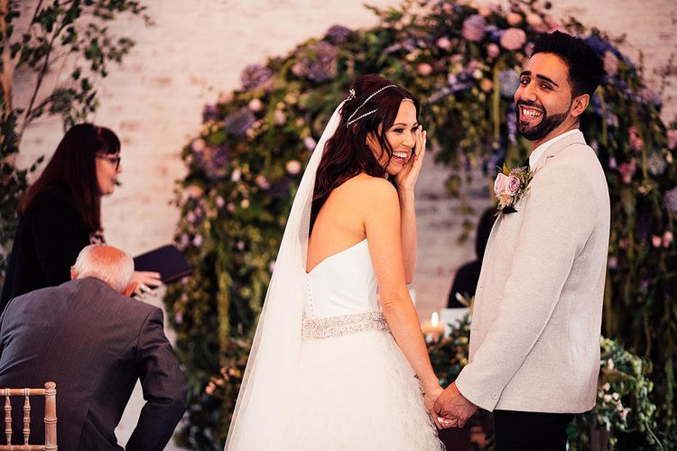 Bride and groom laughing at the altar of their Dorfold Hall wedding ceremony