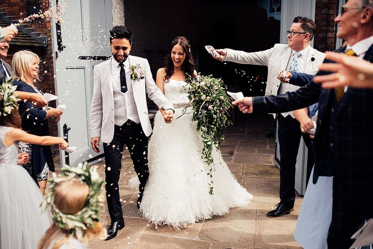 Confetti moment with bride in separates and groom in grey blazer