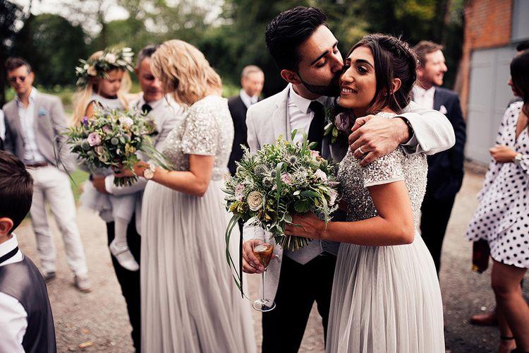 Groom kissing his bridesmaid sister on the cheek