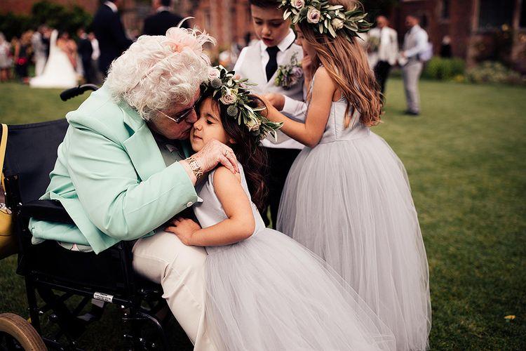Gran kissing her flower girl grand daughter on the cheek
