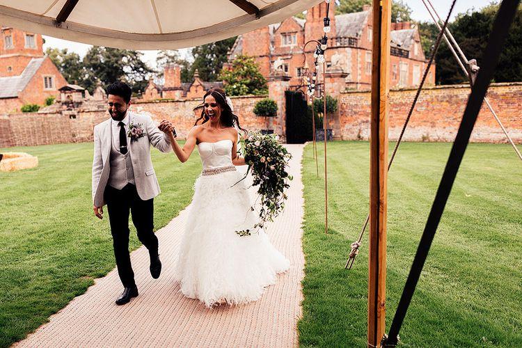 Bride and groom entering the marquee wedding reception