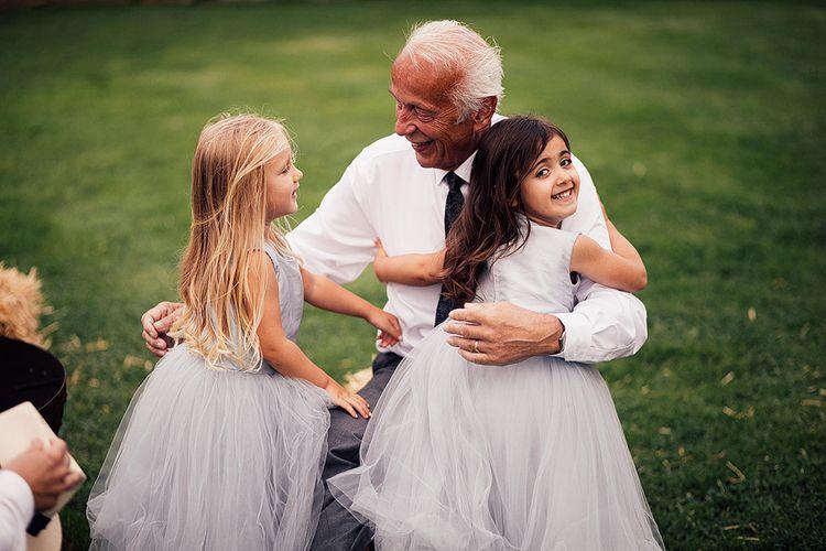 Grandad cuddling the little flower girls in grey tulle dresses