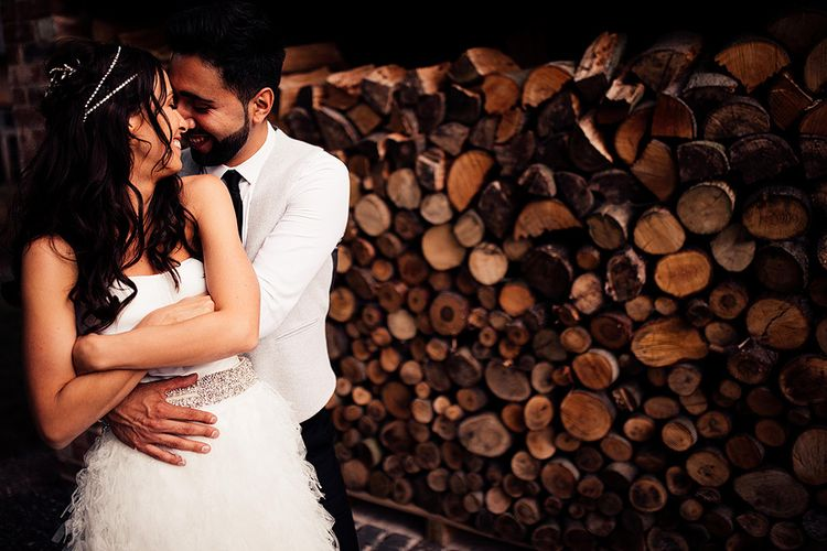 Bride and groom embracing by some logs at Dorfold Hall wedding venue