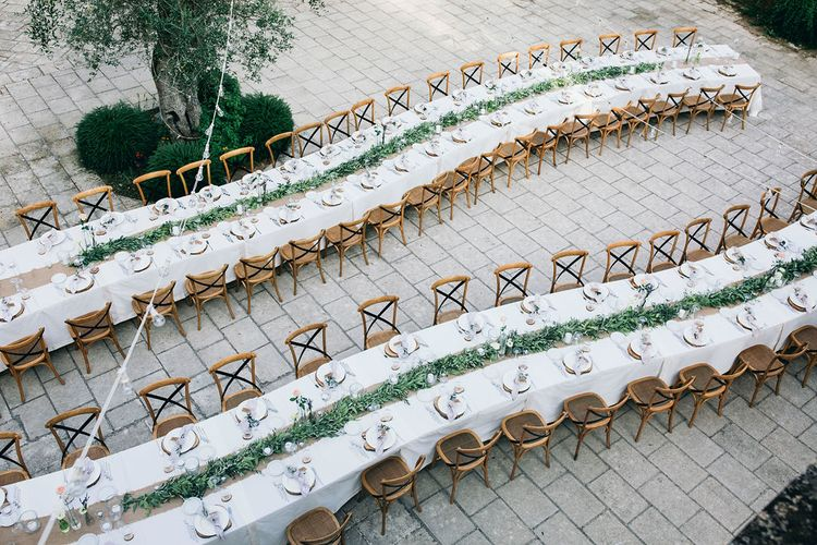 Outdoor Wedding Reception Decor at Tenuta Tresca | Long Tables Snaking Through Courtyard | Foliage Table Runners | Festoon Lights | Knotted Lilac Napkins | Tall Stemmed Candle Holders | Puglian Countryside Wedding with Fairy Light Altar and Olive Grove Aperitivo | Figtree Wedding Photography