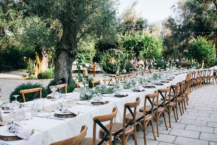 Outdoor Wedding Reception Decor at Tenuta Tresca | Long Tables Snaking Through Courtyard | Foliage Table Runners | Festoon Lights | Wood Slice Place Settings | Knotted Lilac Napkins | Tall Stemmed Candle Holders | Fairy Light Moon Gate | Puglian Countryside Wedding with Fairy Light Altar and Olive Grove Aperitivo | Figtree Wedding Photography