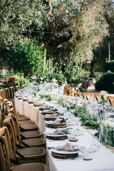 Outdoor Wedding Reception Decor at Tenuta Tresca | Long Tables Snaking Through Courtyard | Foliage Table Runner | Wood Slice Place Mats | Tall Stemmed Candle Holders | Festoon Lights | Puglian Countryside Wedding with Fairy Light Altar and Olive Grove Aperitivo | Figtree Wedding Photography