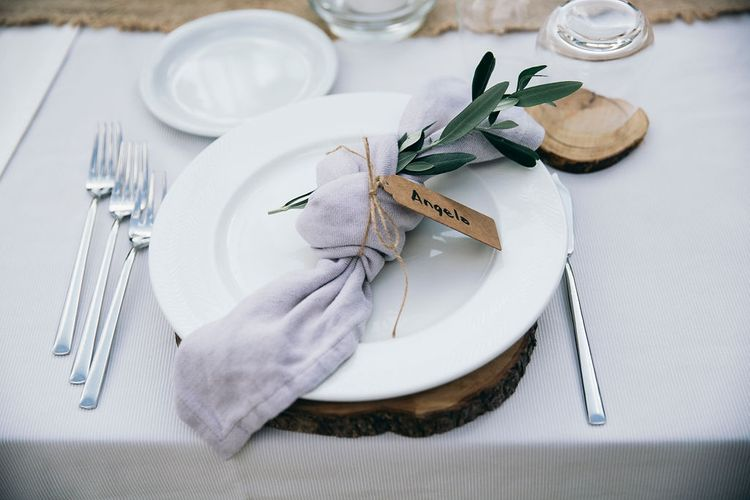 Outdoor Wedding Reception Decor at Tenuta Tresca | Wood Slice Place Mats | Knotted Lilac Napkin with Greenery | Kraft Label and Twine | Puglian Countryside Wedding with Fairy Light Altar and Olive Grove Aperitivo | Figtree Wedding Photography