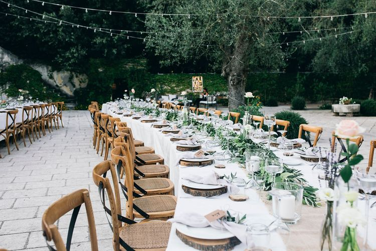 Outdoor Wedding Reception Decor at Tenuta Tresca | Long Tables Snaking Through Courtyard | Foliage Table Runners | Festoon Lights | Knotted Lilac Napkins | Wood Slice Place Mats | Tall Stemmed Candle Holders | Puglian Countryside Wedding with Fairy Light Altar and Olive Grove Aperitivo | Figtree Wedding Photography
