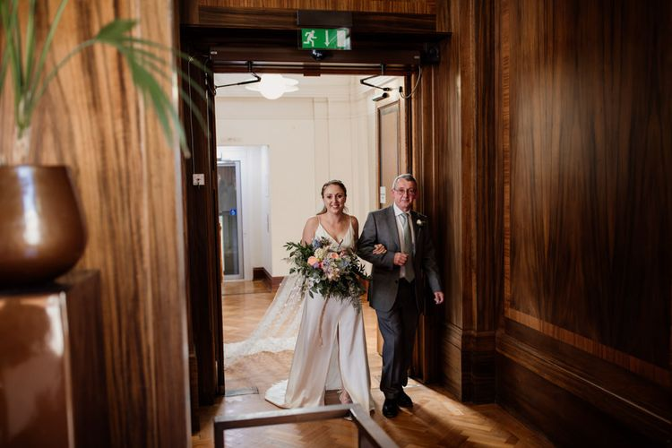 Bride entering town hall ceremony in London wearing split front gown and polka dot veil
