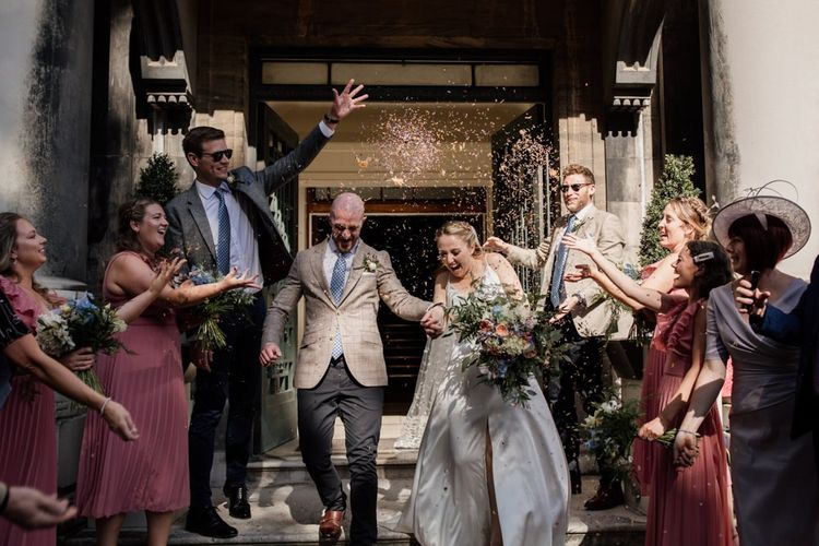 Confetti shot at town hall London wedding with split front gown and polka dot veil