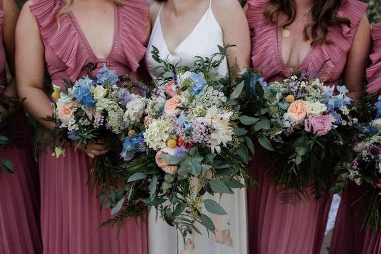 Pink pleated bridesmaid dresses with David Austin rose floral bouquets at West Reservoir Centre wedding
