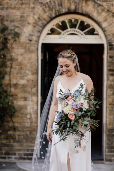 Bride wearing a simple split front dress and polka dot veil for West Reservoir Centre wedding