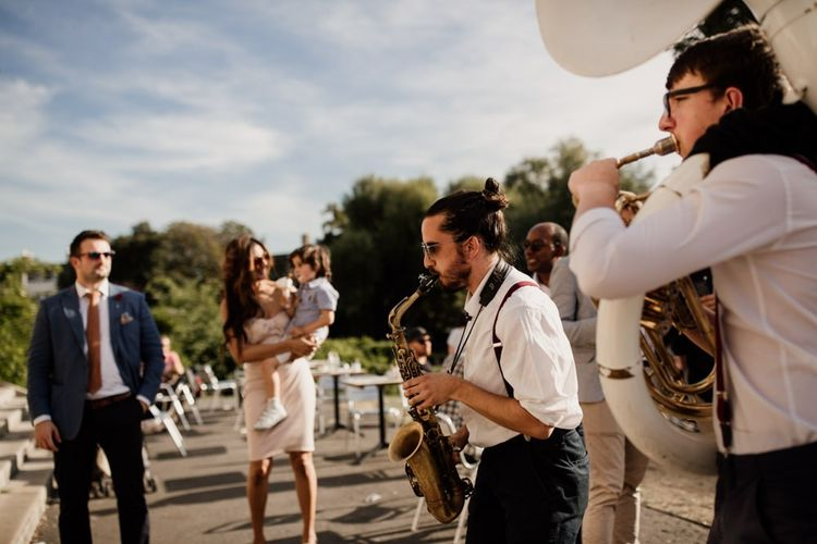 Five piece marching band through the park to West Reservoir Centre wedding