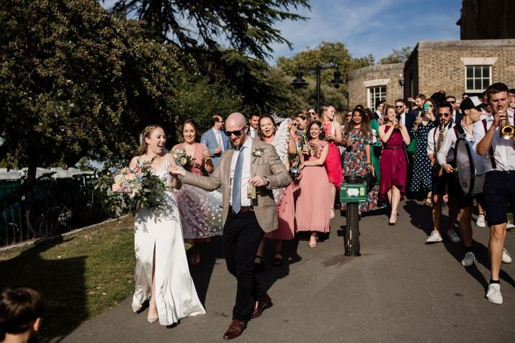 Bride and groom with their guests and five piece marching band walking through the park to West Reservoir Centre wedding