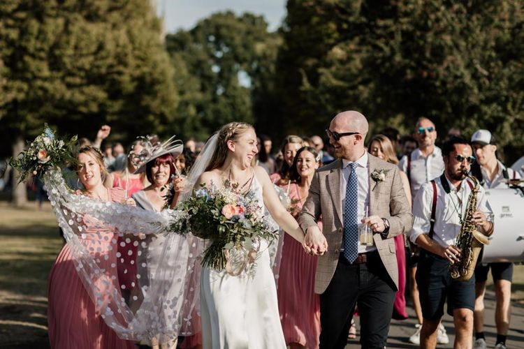 Bride wearing polka dot veil with pink bridesmaid dresses for city wedding with marching band