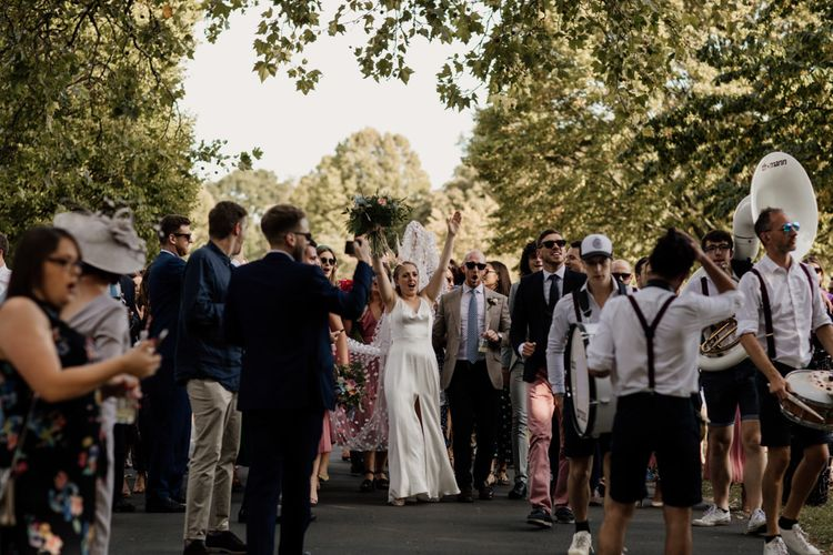 Bride wearing split front dress for city wedding with marching band